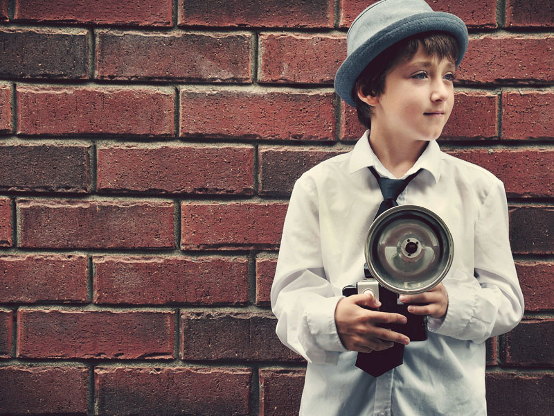 un enfant tient une vieille caméra photo