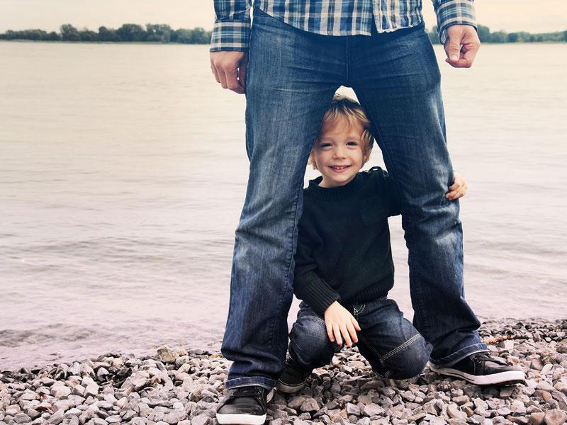 un petit garçon entre les jambes de son papa