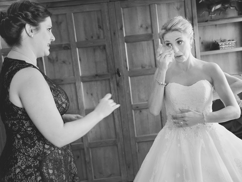 bride getting emotional while getting dressed