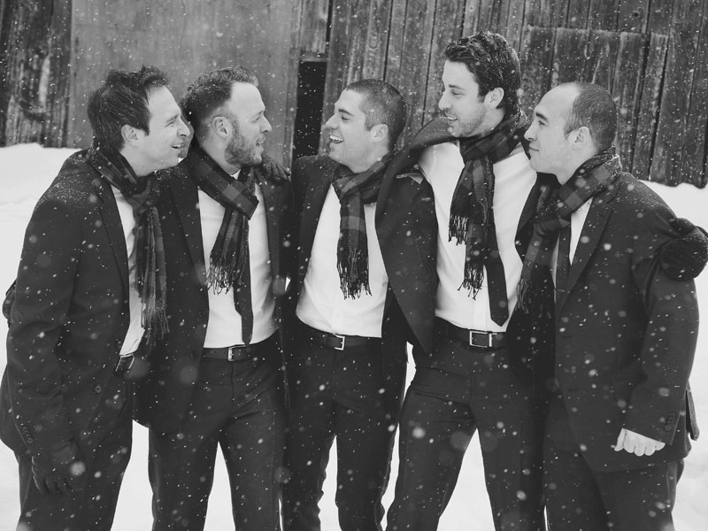 groom with groomsmen chatting in snow