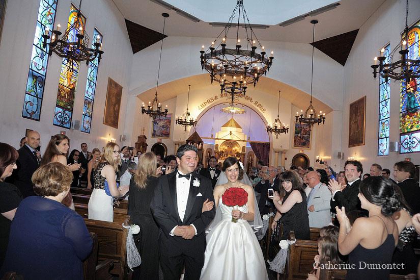 les mariés marchent dans l'allée de l'église