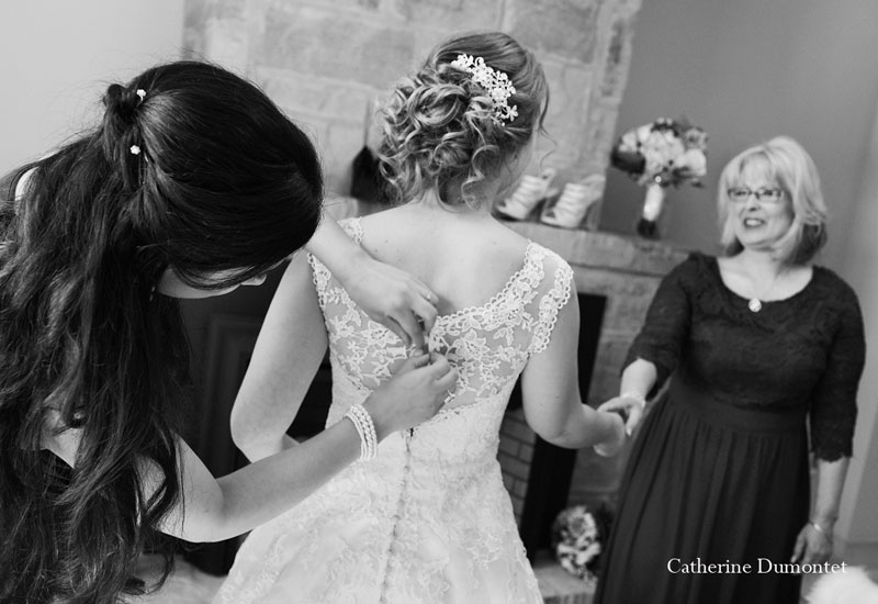 bride getting dressed with her mom