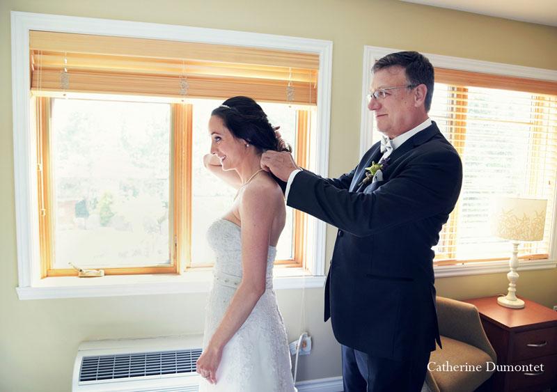 Le père de la mariée l'aide à attacher son collier