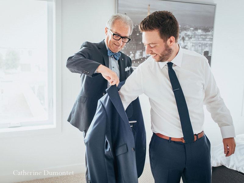 Le père du marié l'aide à s'habiller