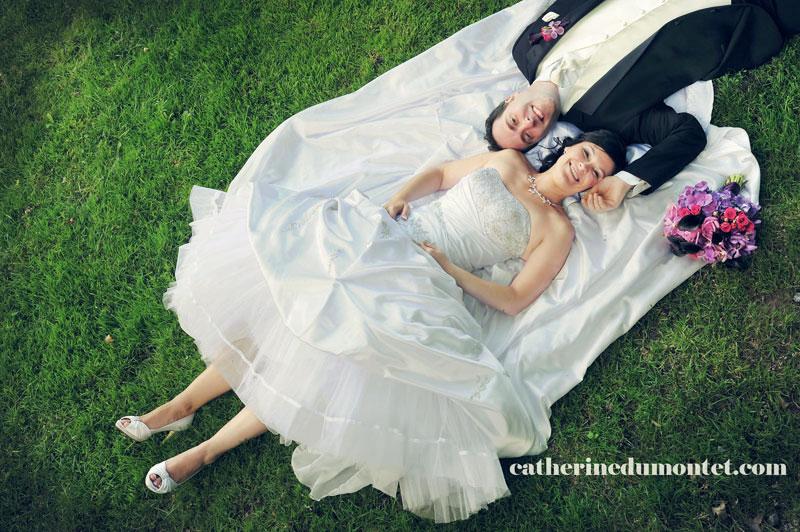 les nouveaux-mariés allongés dans l'herbe