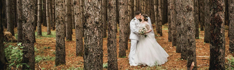 un couple de mariés s'embrassent dans la forêt