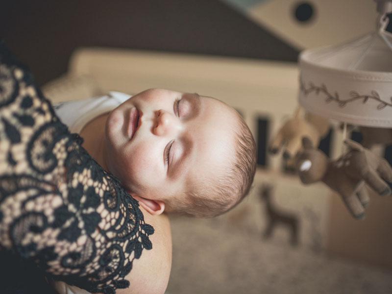 bébé dormant dans les bras de sa mère