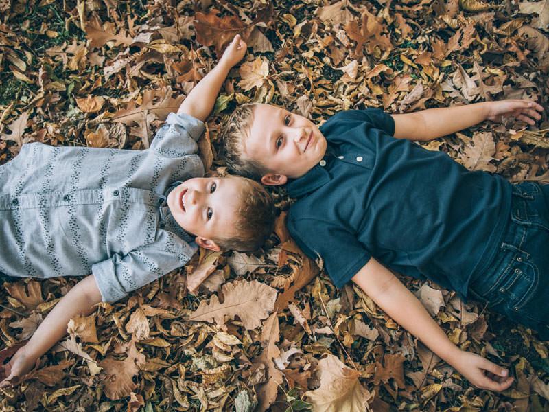 deux frères dans les feuilles d'automne