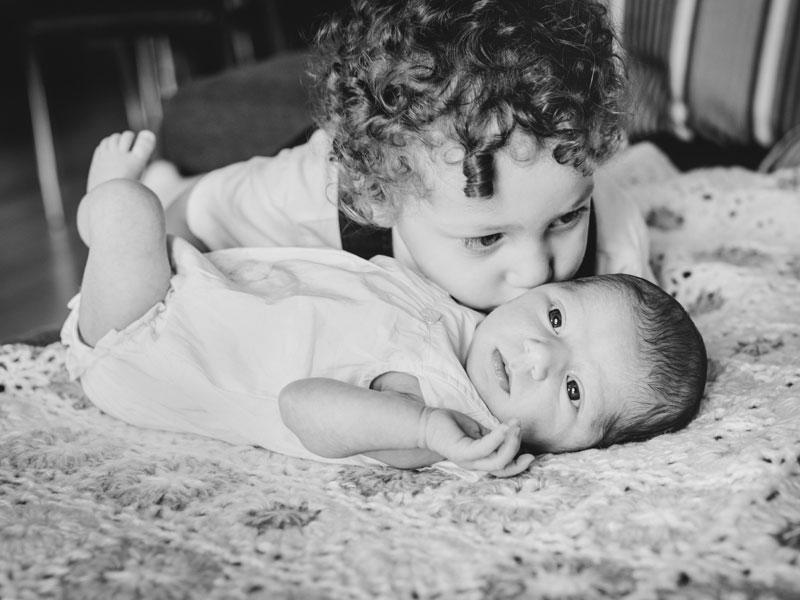 petit frère qui embrasse sa bébé soeur