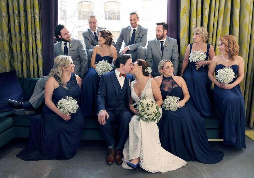 les mariés s'embrassent entourés de leur cortège