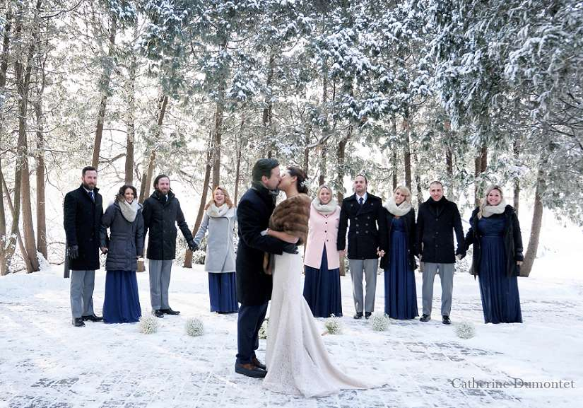 Le couple s'embrasse devant leur cortège dans la neige