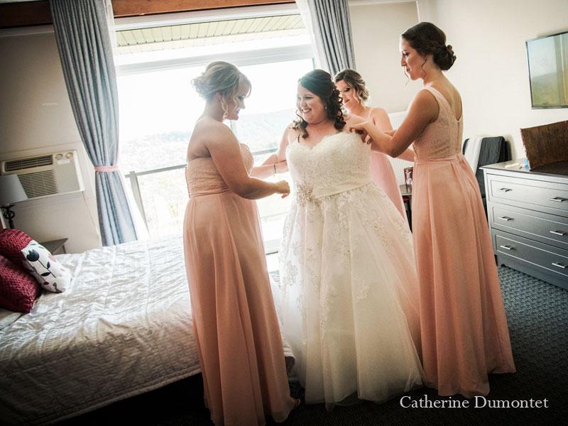 la mariée s'habille avec l'aide de ses filles d'honneur