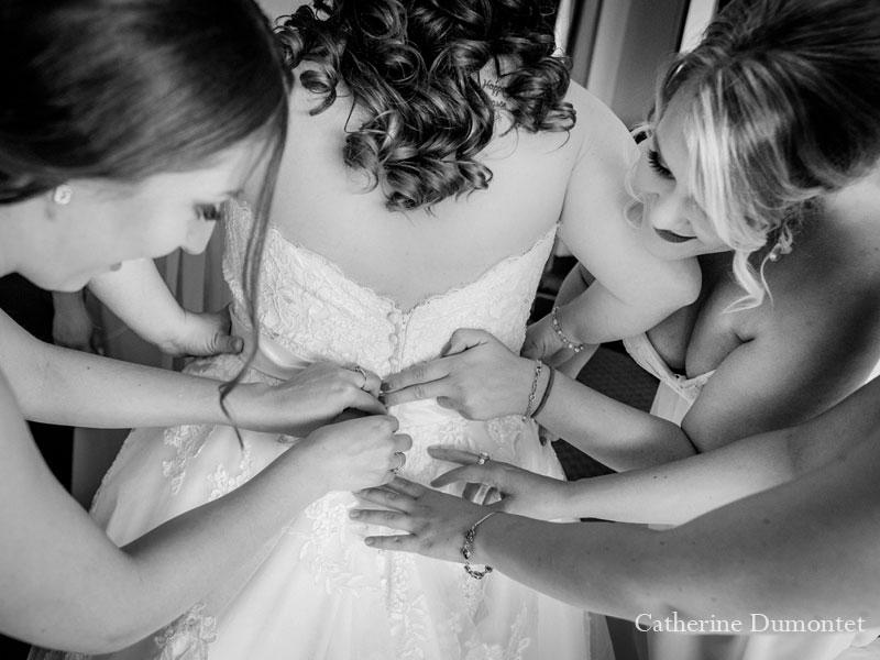 les demoiselles d'honneur boutonnent la robe