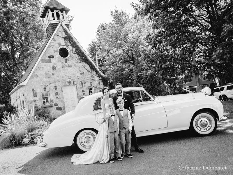 Les mariés à l'église devant la limousine