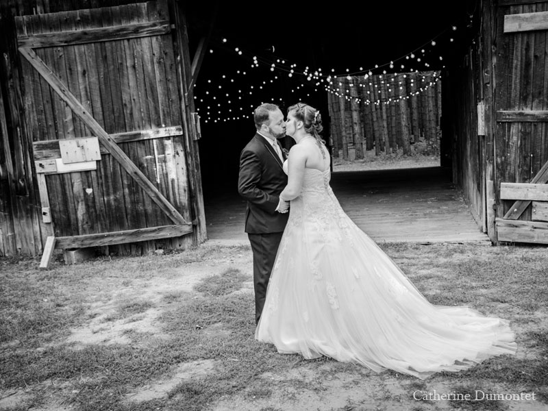 Bride and groom kissing in front of barn